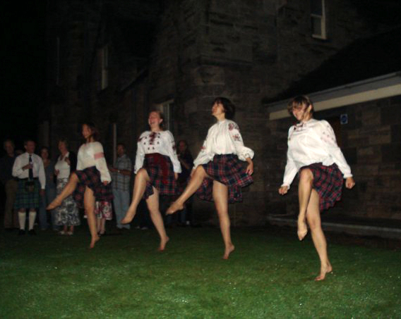 Ukrainian dancers performing an Irish dance in Ukrainian-Scottish costumes, to a Russian song, on the Scottish lawn